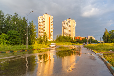 Wet road after the rain and two houses in Nizhny Novgorod, Russia Stock Photo