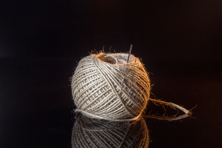 A ball of coarse thread with a needle on black background Фото со стока