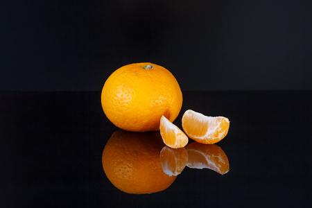 Mandarin with reflection on black background