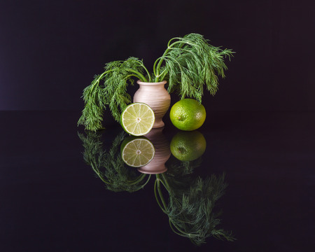 Dill in a vase and lime with reflection on black background Фото со стока