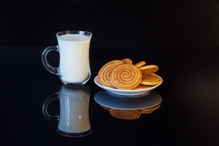 A cup of milk and round shortbread