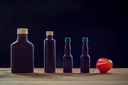 Dark bottles wirh physalis on a dark background