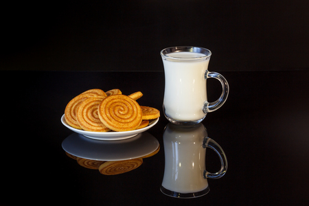 Milk with cookies on a dark background