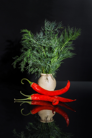 Dill and hot pepper with reflection on black background