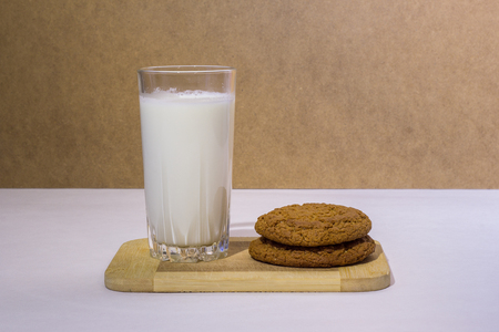 Glass of milk and cookies on a wooden board