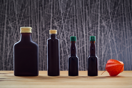 Four dark bottles and physalis on the table