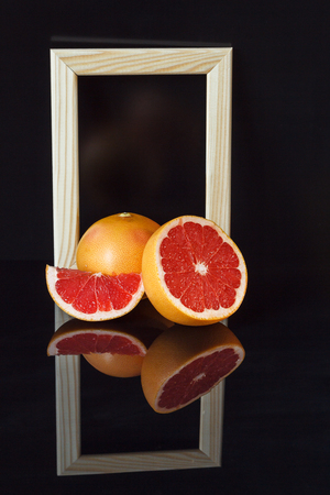 Frame, grapefruit with reflection on a dark background