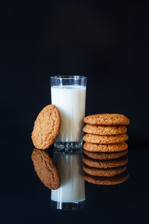 Oatmeal cookies and a glass of milk on a black background Фото со стока