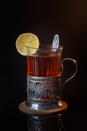 Tea with lemon in a glass with a cup holder