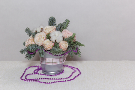 Bucket with pale pink roses with fir branches on light coloured background