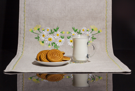 Cup of milk with cookies on a barkless tablecloth with embroidery Фото со стока