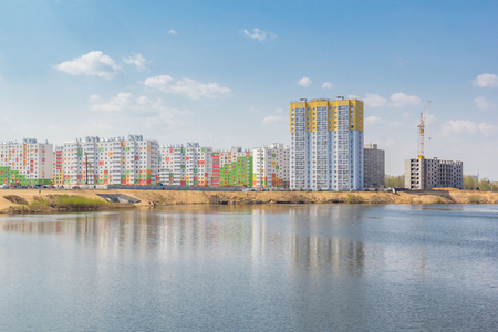 Residential buildings with reflection on the lake in the city Фото со стока