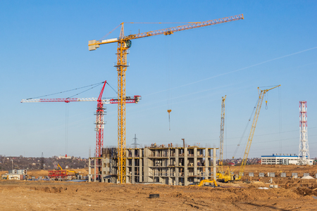 Cranes on a residential building construction site, Russia Фото со стока