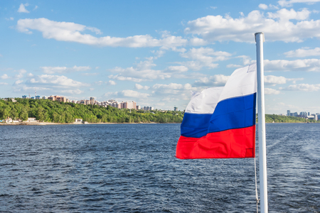 Russian flag on the background of the Volga River and the city of Samara at sunny day Фото со стока