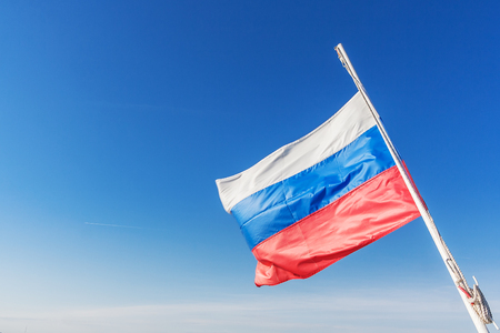 Russian tricolor develops in the wind in a clear sky