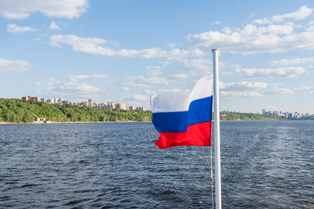 Flag of Russia develops in the wind against the background of the city and the river