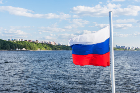 Russian flag on flagpole on the background of the river, shore and sky