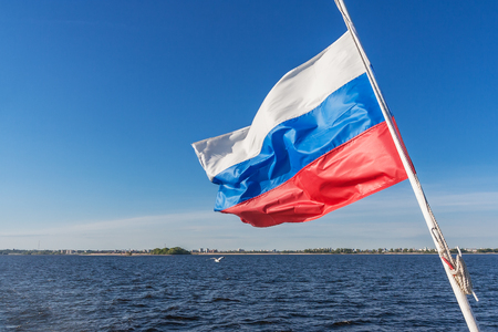 Russian flag on the background of the river and the shore in the wind Фото со стока