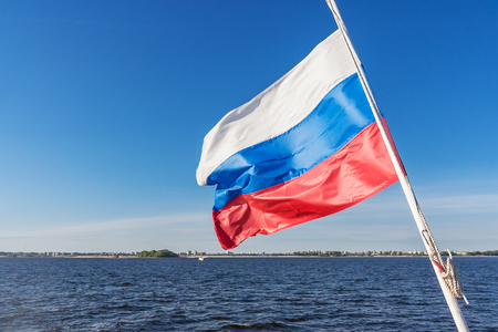 Flag of the Russian Federation illuminated by the sun against the background of the river and the sky Фото со стока