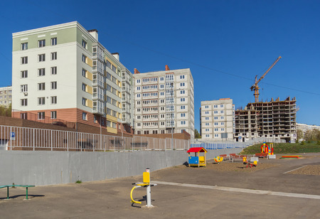 Residential buildings under construction with a playground in front of him