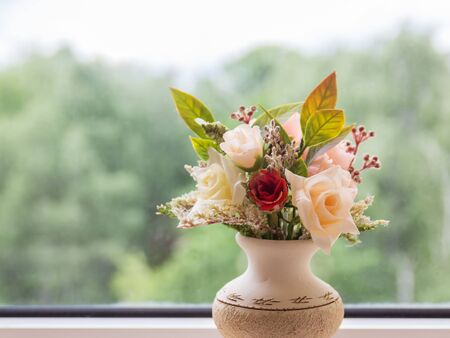 Vase of flowers on the background of an open window with a summer landscape