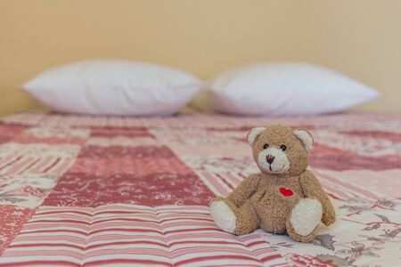 Teddy bear and two pillows on a bed with a pink and white bedspread