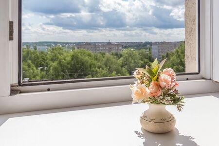 Open window with cityscape and flower on the window