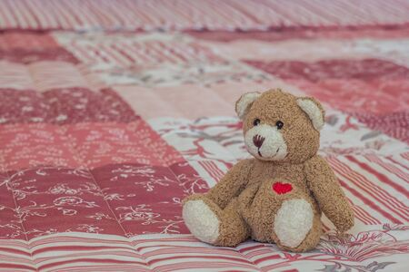 Toy bear on a pink and white bedspread at hotel