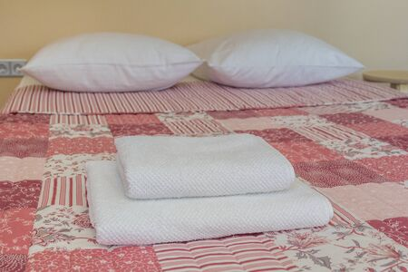 Clean white towels and two pillows on the bed in a cozy room