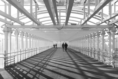 Silhouettes of people in a tunnel in black and white Редакционное