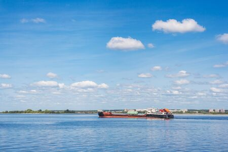 Cargo ship goes down the river in spring