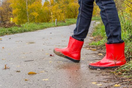 Walking in red rubber boots in the fall