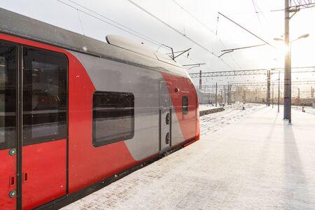 Train and sun on a winter morning on a platform Фото со стока