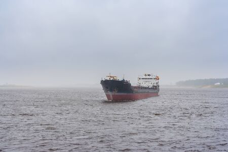 Cargo ship on the river in the fog