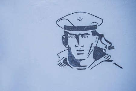 Image of a sailor at a war memorial, on a gray wall