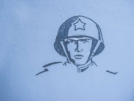 Image of a soldier at the war memorial, on a gray wall Редакционное