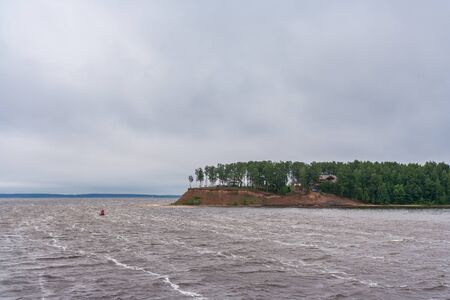 Waves on the river near the green peninsula on the Volga River at summer