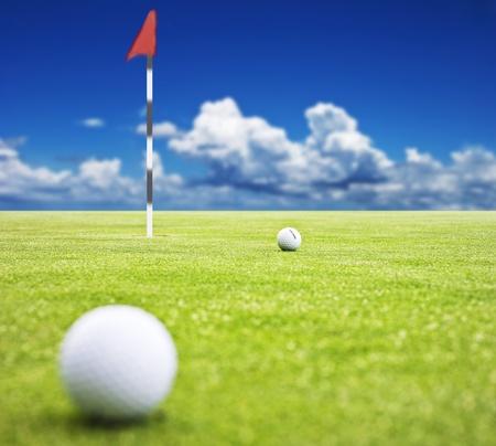Pallina da golf su un putting green con il flag in background - molto basse profondità di campo
