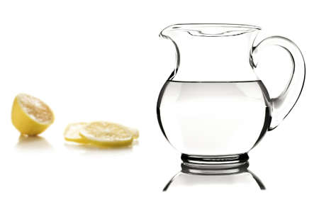 Glass pitcher with water and lemon slices on white photo