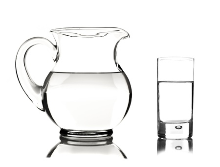 Glass and glass pitcher on white background with space for text