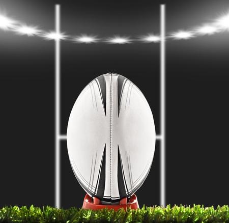 pelota rugby: Bal�n de rugby con objetivo puestos bajo luces en el campo de noche