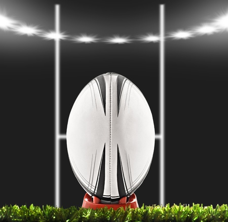 Rugby ball with goal posts under lights on the field at night Stock Photo