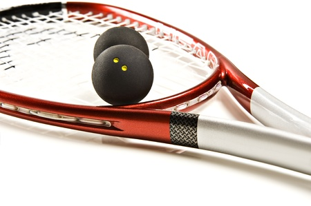 Close up of a red and silver squash racket and ball on a white background with space for text Standard-Bild