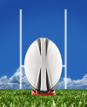 Rugby ball on field with goal posts photo