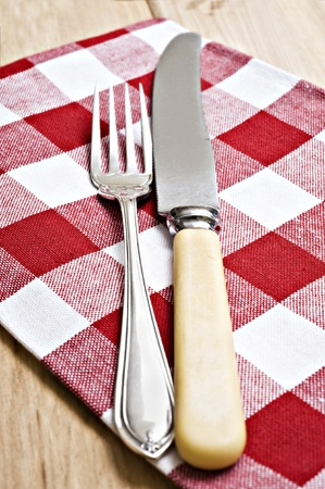 Antique knife and fork on a red and white cloth photo