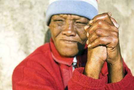 An old African woman with folded hands - focus on the weathered hands