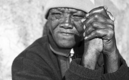 gente pobre: Foto blanco y negro de una mujer africana senior con manos plegadas - foco en las manos de degradado Foto de archivo