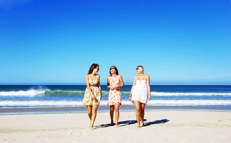 Three young woman having fun on the beach on a summer day Stock Photo