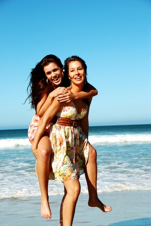 Two young woman having fun on the beach on a summer day