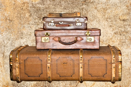 Three old leather suitcases on a grunge background photo